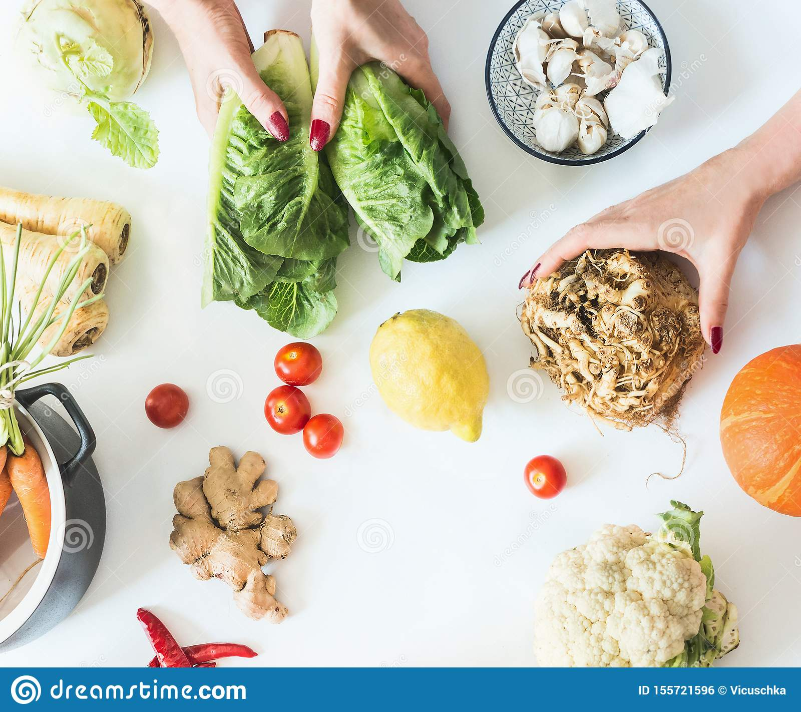 Female girls hands holding various low carb vegetables on white background with pot, top view. Flat lay. Tasty diet cooking.