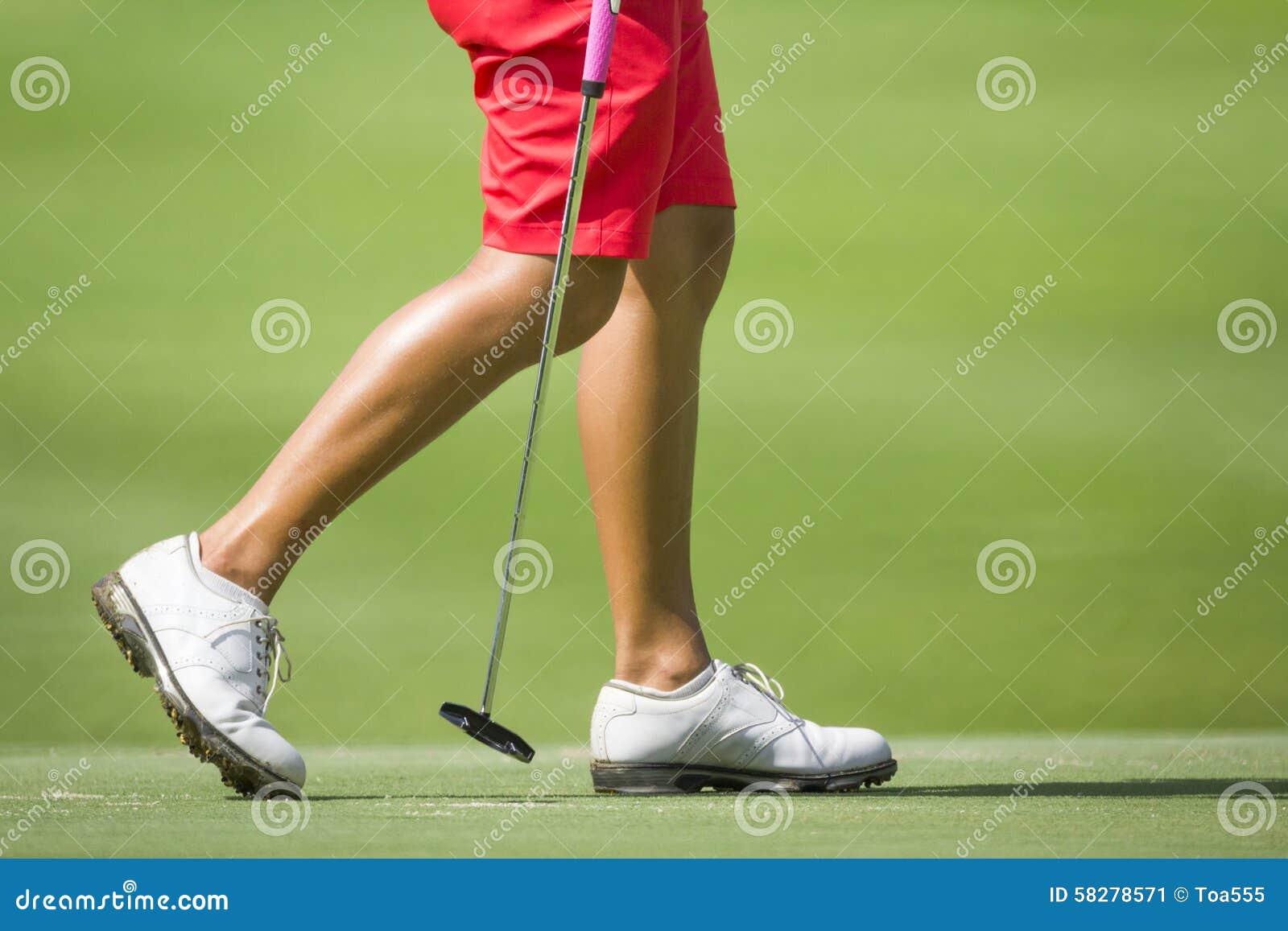 Female golfers walking on green.
