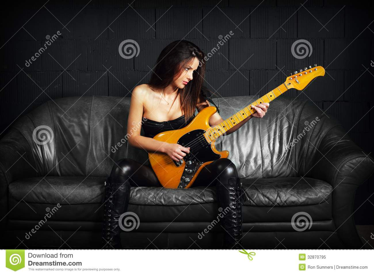 Female Guitarist Sitting On A Leather Couch Royalty Free ...