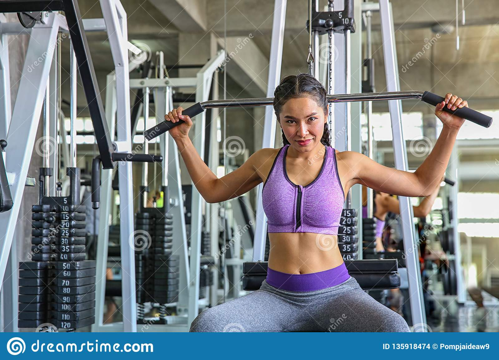 Female in gym. sport, fitness, bodybuilding, woman exercising and flexing muscles on machine in gym. asian girl. Asian girl