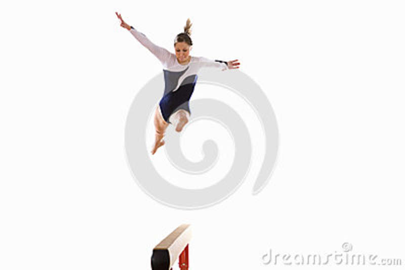 Female Gymnast Performing Jump On Balance Beam Low Angle