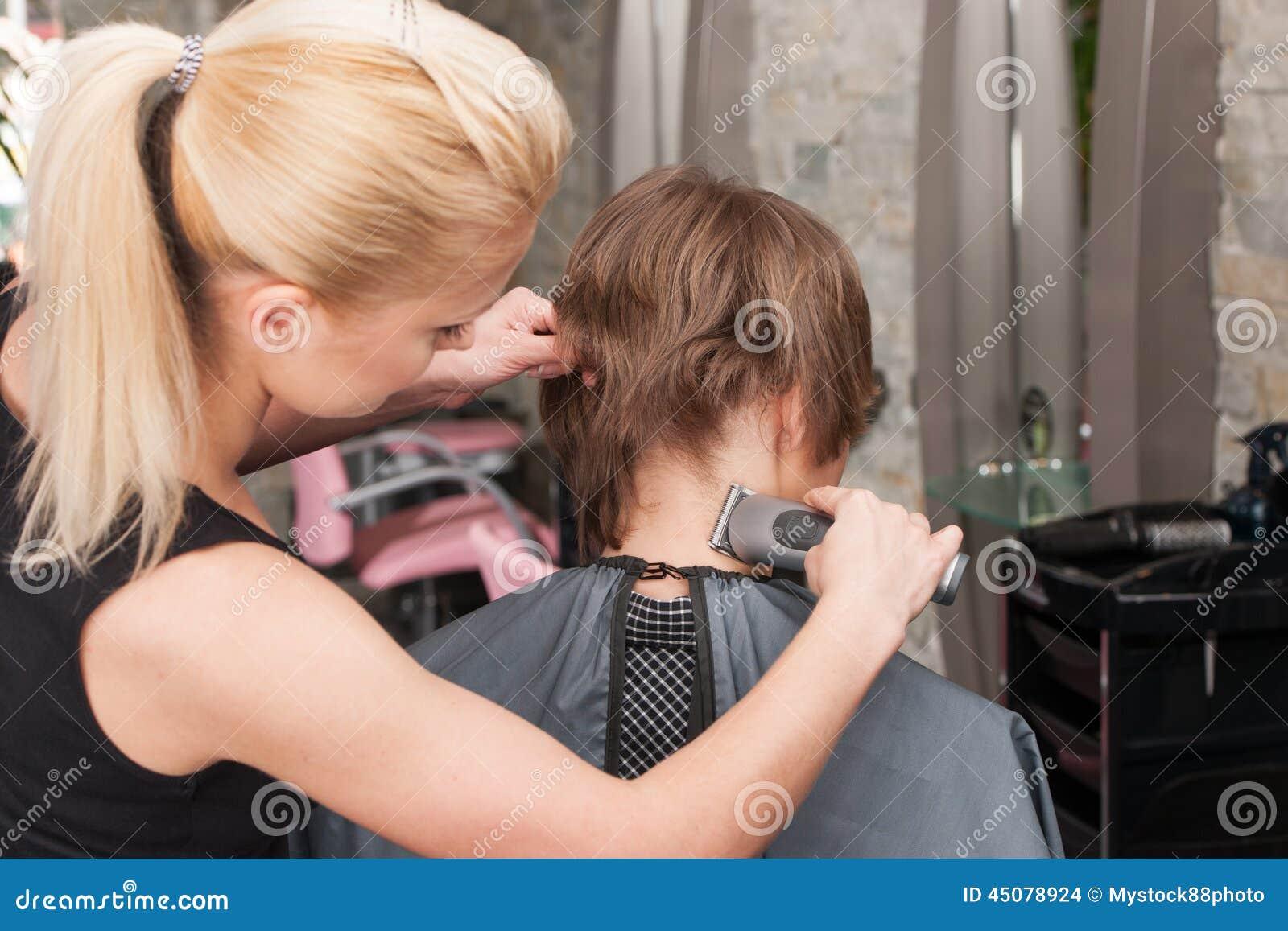 Female Hairdresser Cutting Hair Of Man Client Using