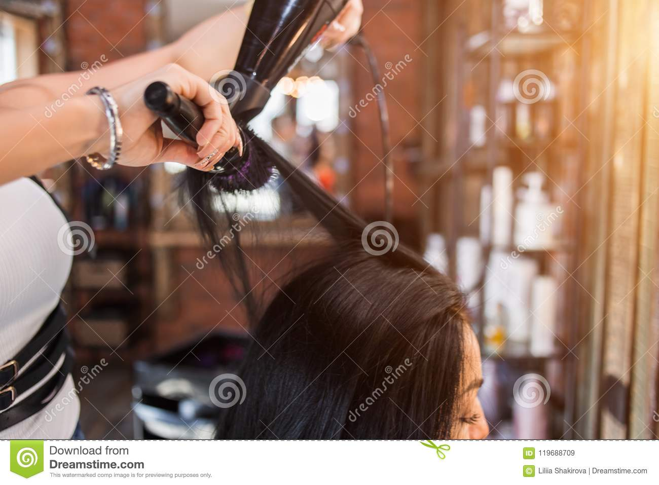 Female hairdresser making hairstyle to girl in beauty salon.