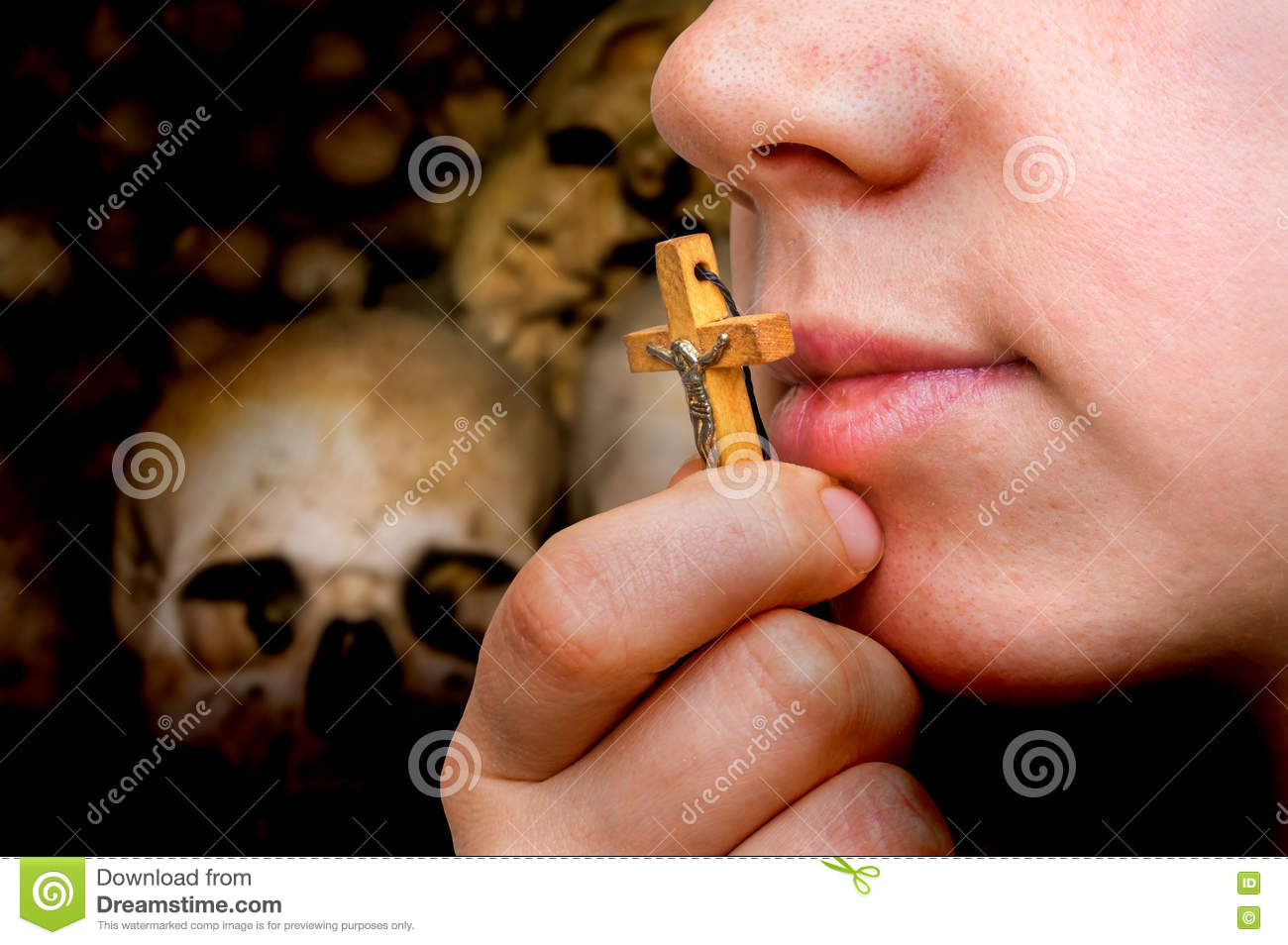 Female hand with cross on skulls and bones background
