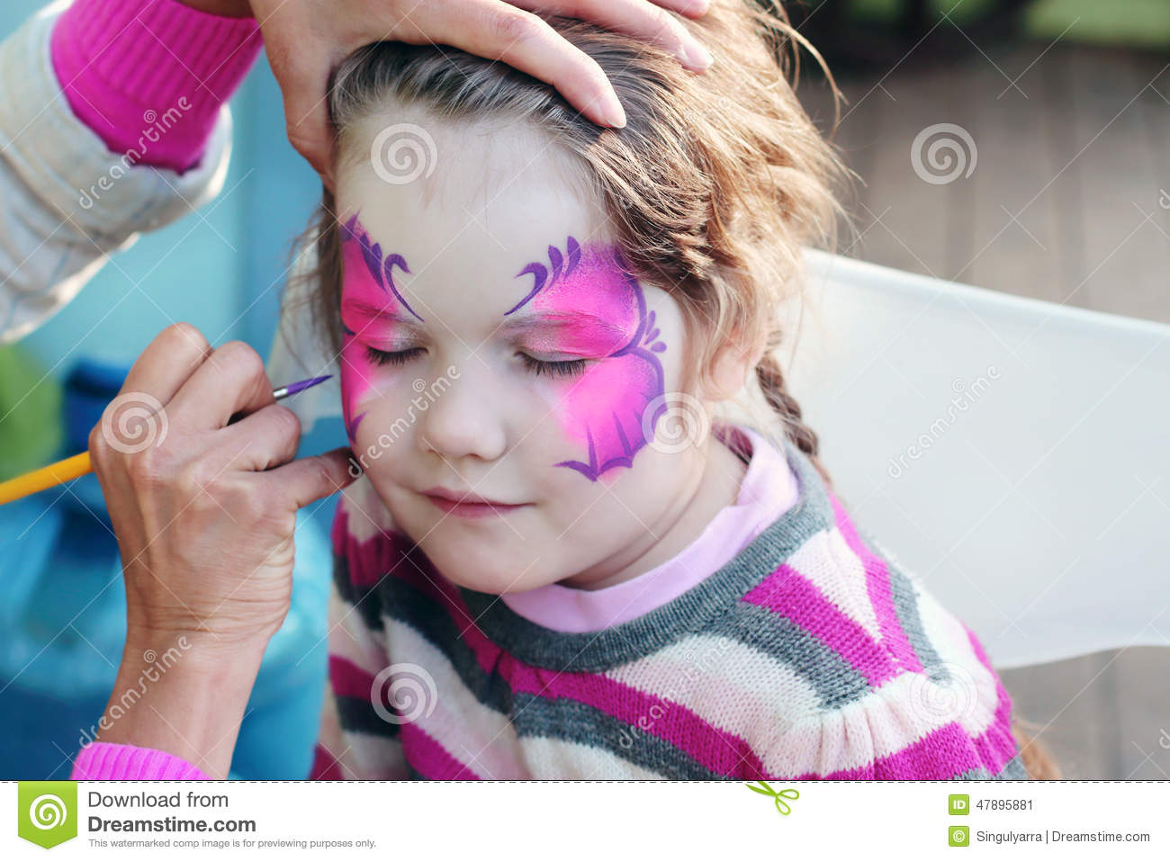 Female hand drawing purple butterfly on face