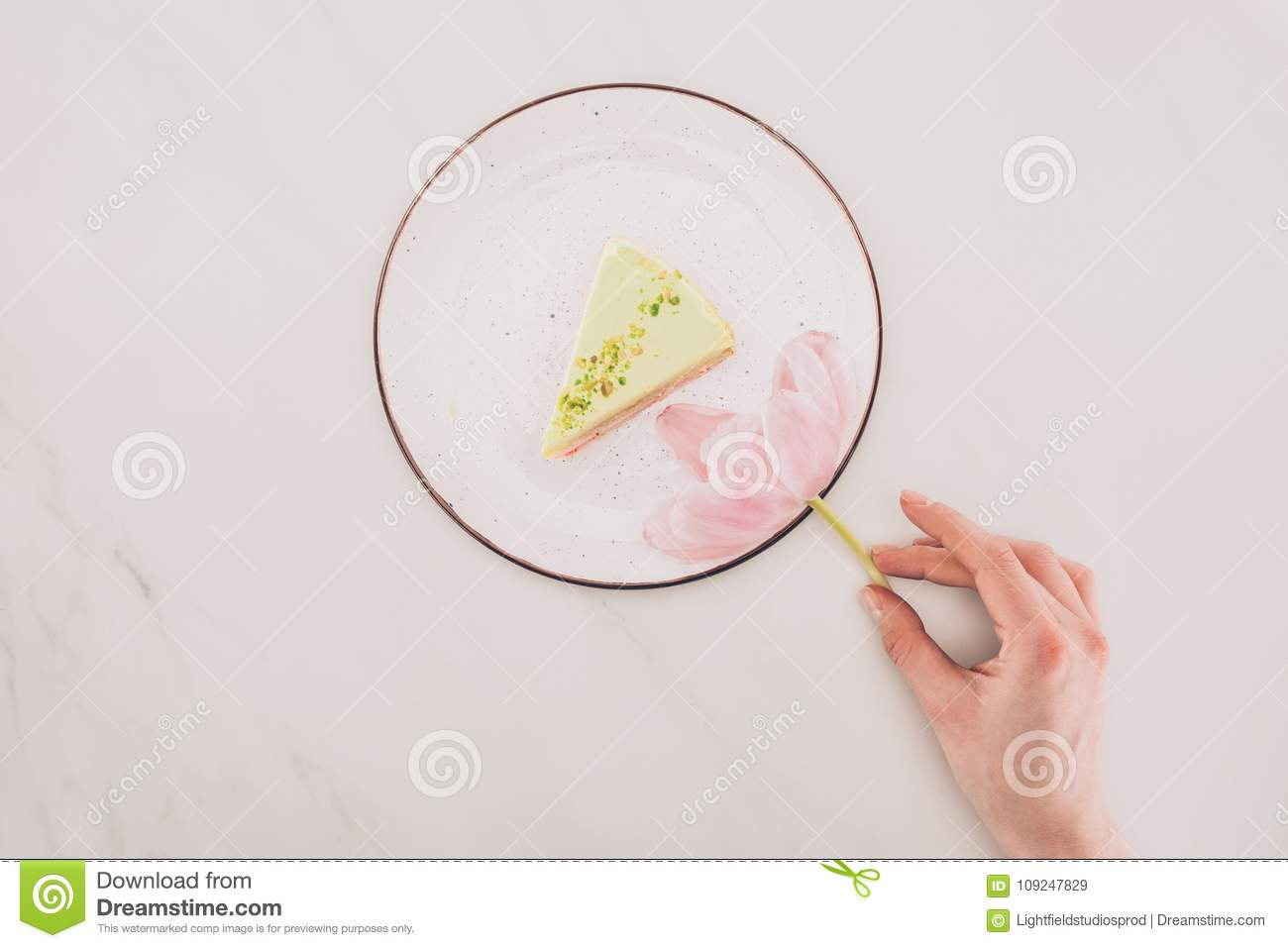 Female hand, flower and piece of cake on plate on white tabletop