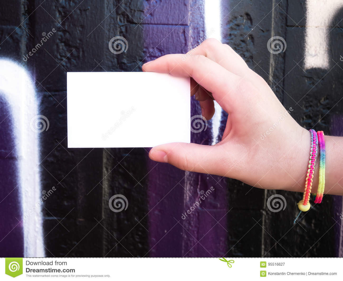 Female hand holding blank white business card.