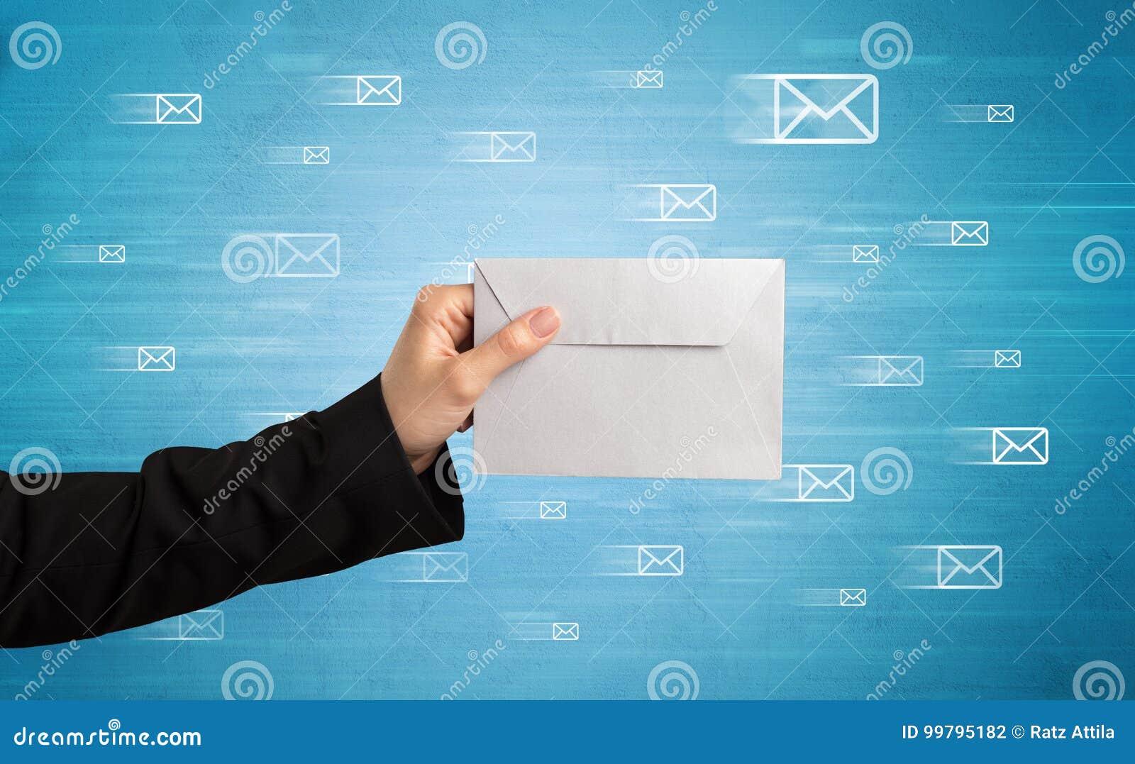 Hand holding envelope with message symbols around