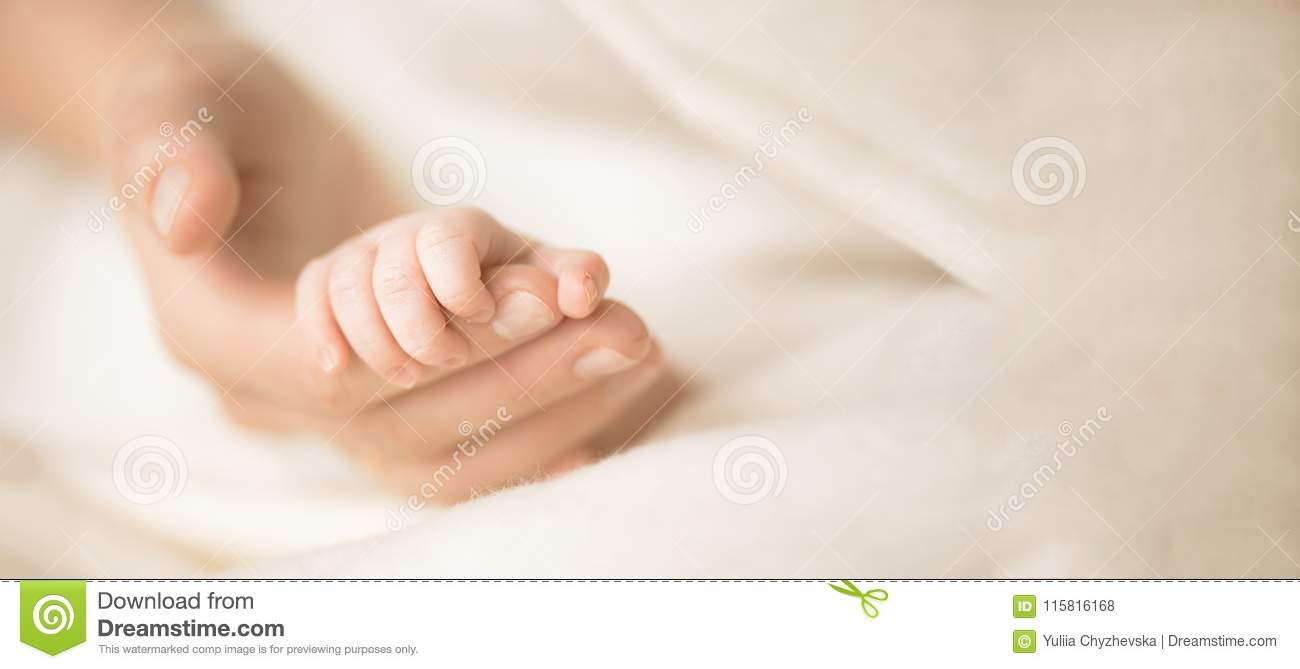 Female hand holding her newborn baby`s hand. Mom with her child. Maternity, family, birth concept. Copy space for your