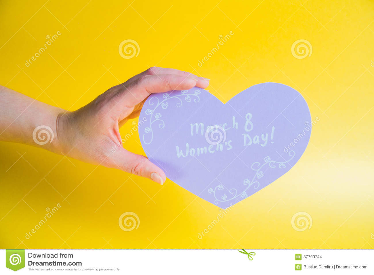 Female hand holding pink paper heart on golden background - Happy Women`s Day