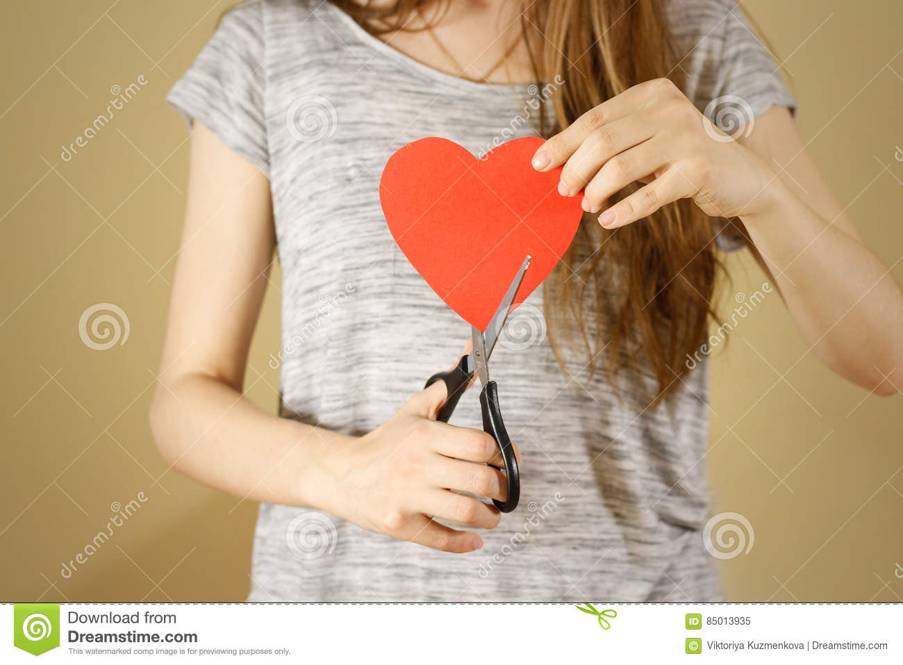 Female hand holding red Valentines card with heart on b