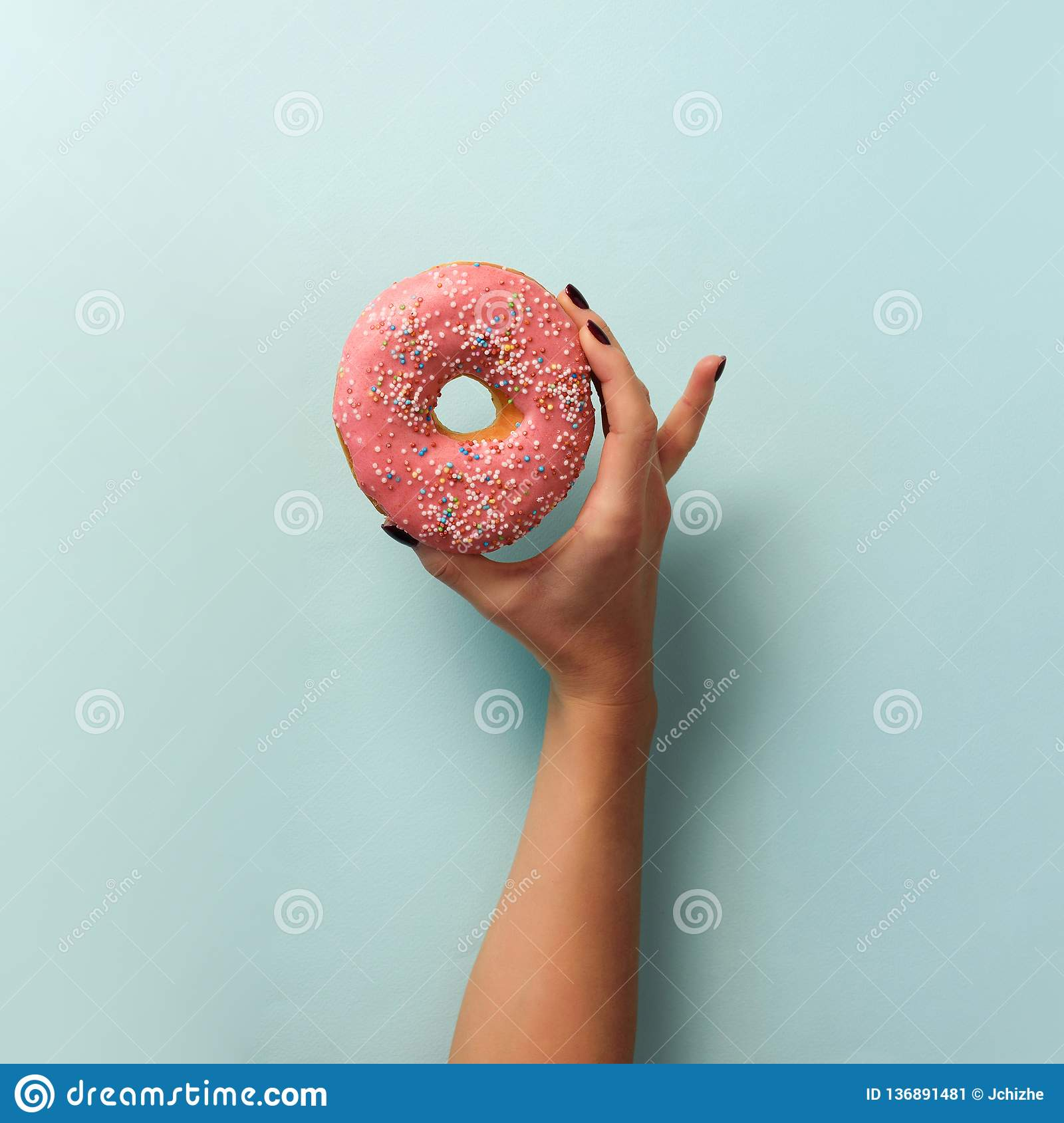 Female hand holding sweet donut over blue background. Top view, flat lay. Square crop. Weight lost, sport, fitness, diet concept.