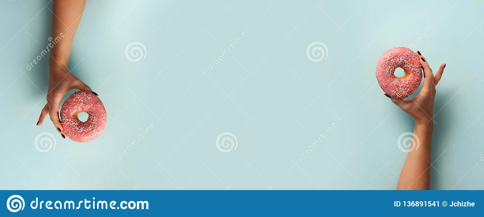 Female hand holding sweet donut over blue background. Top view, flat lay. Weight lost, sport, fitness, diet concept. Banner with