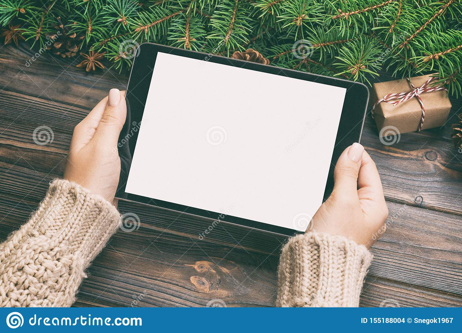 Female hand holding tablet, perspective view. Winter holidays sales background. Christmas online shopping. Toned