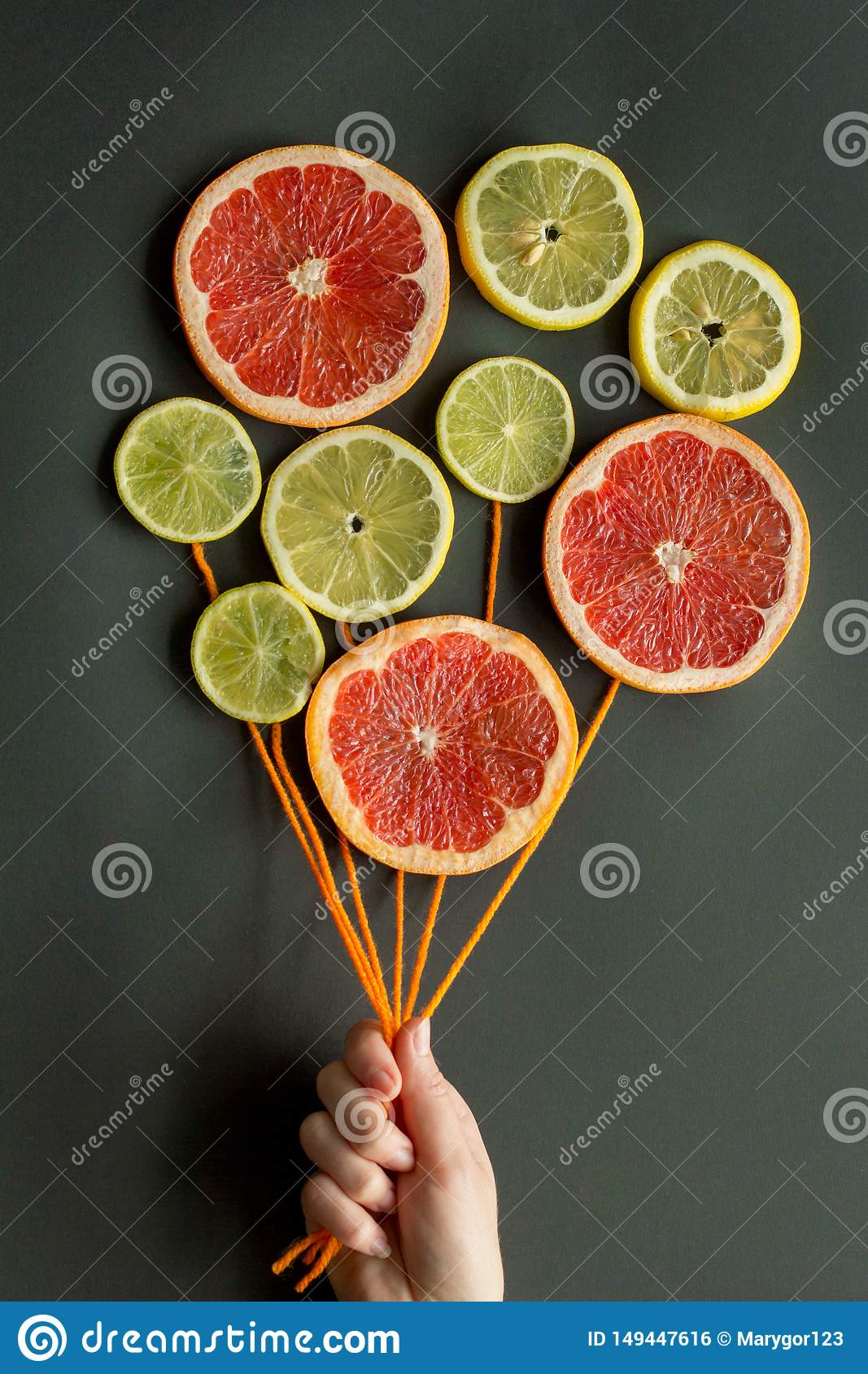 A female hand holds air balloons with orange threads made of citrus slices lemon, lime, orange, grapefruit on a black background