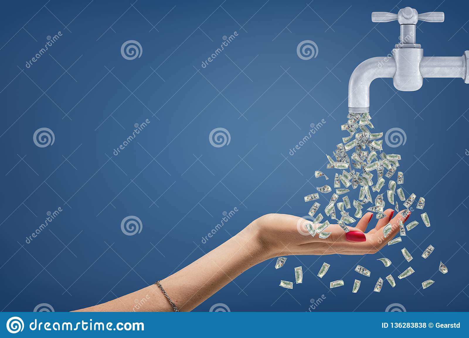 A female hand holds her hand under a stream of money flowing from a metal tap.