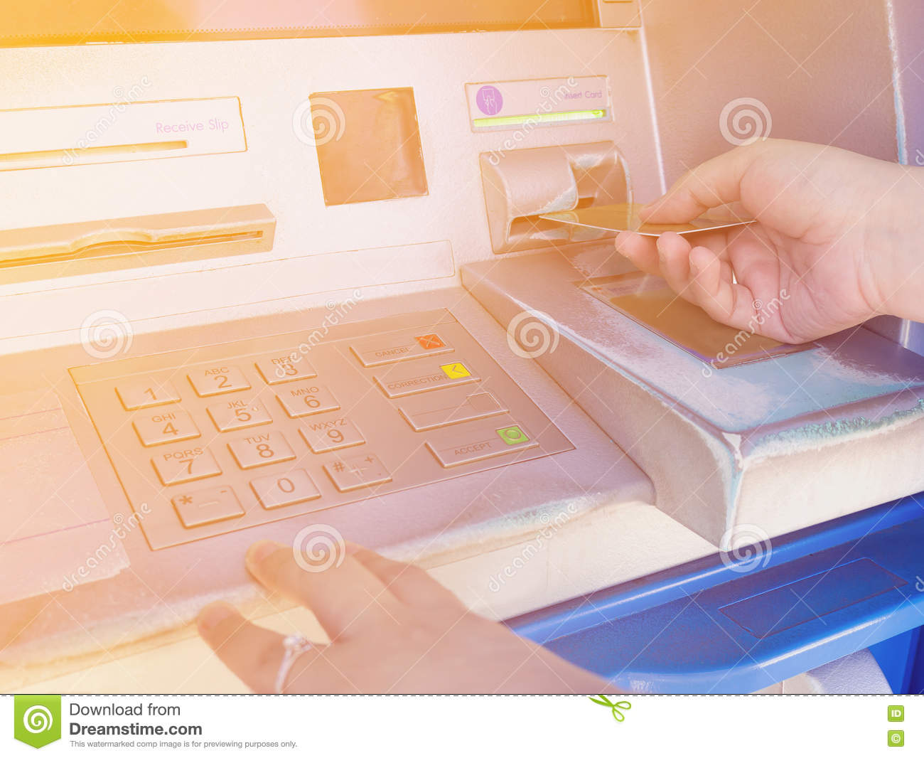 Female hand inserting ATM card into ATM bank machine