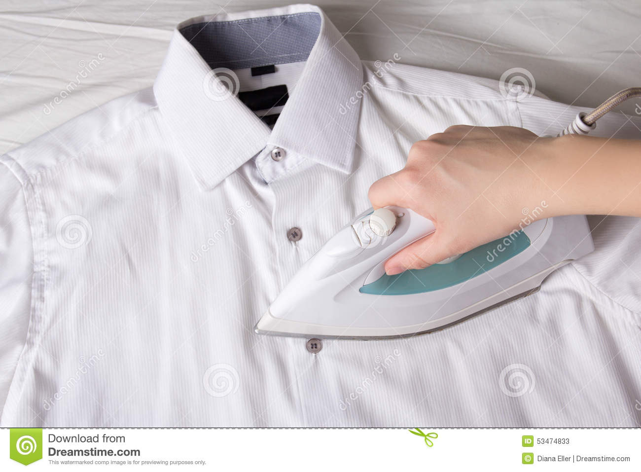 female hand with iron ironing cotton shirt stock photo
