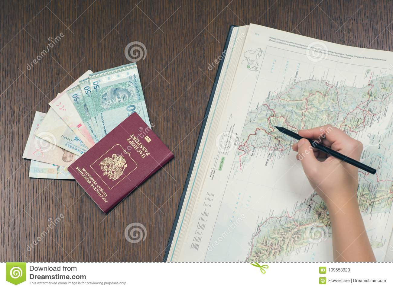 Female hand making a sign on the map of Malaysia for planning a trip. Russian biometric passport, Malaysian money on a background