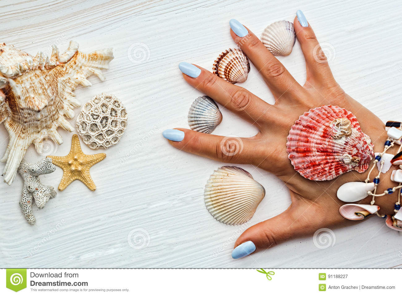Female hand with manicure and sea shells between fingers