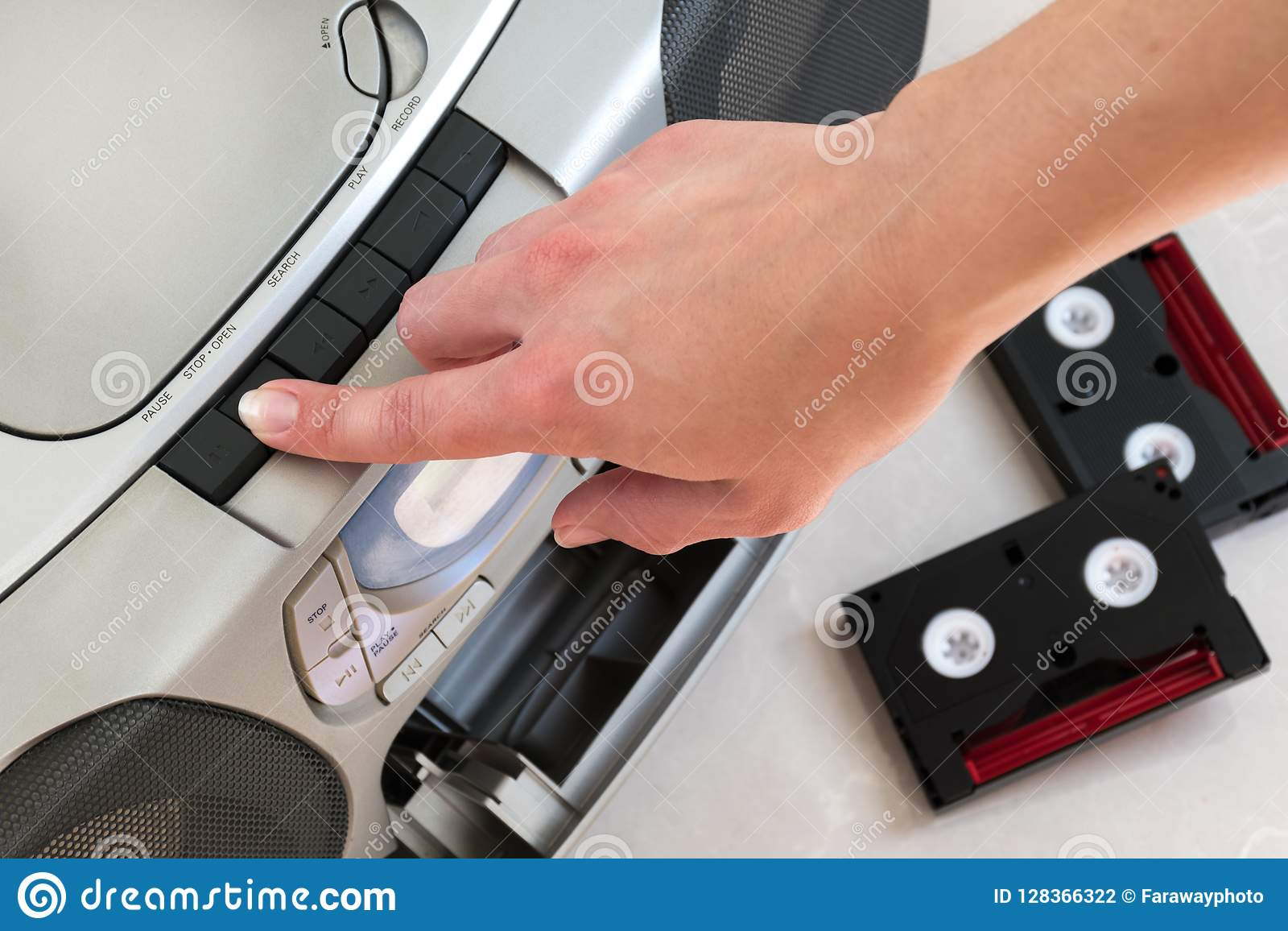 Female hand pushing open button on a grey music center with two black and red cassettes