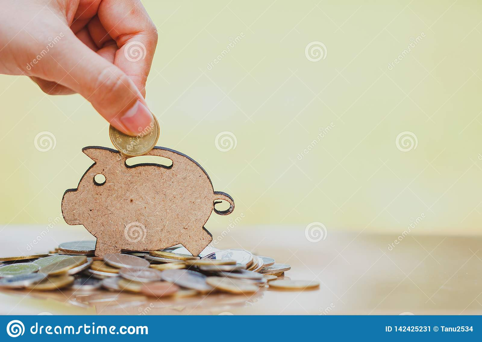 Female hand putting coin and stack of coins in concept of savings and money growing or energy save.