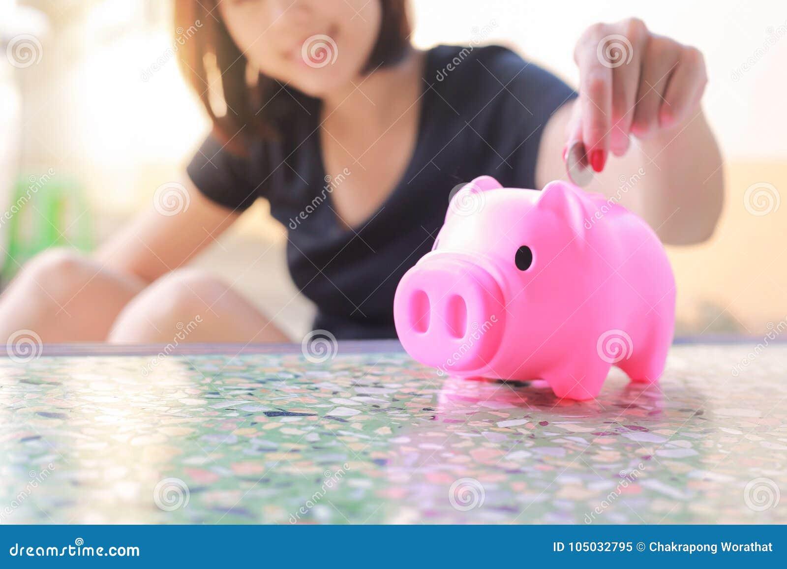 female hand putting money into piggy bank  stock image