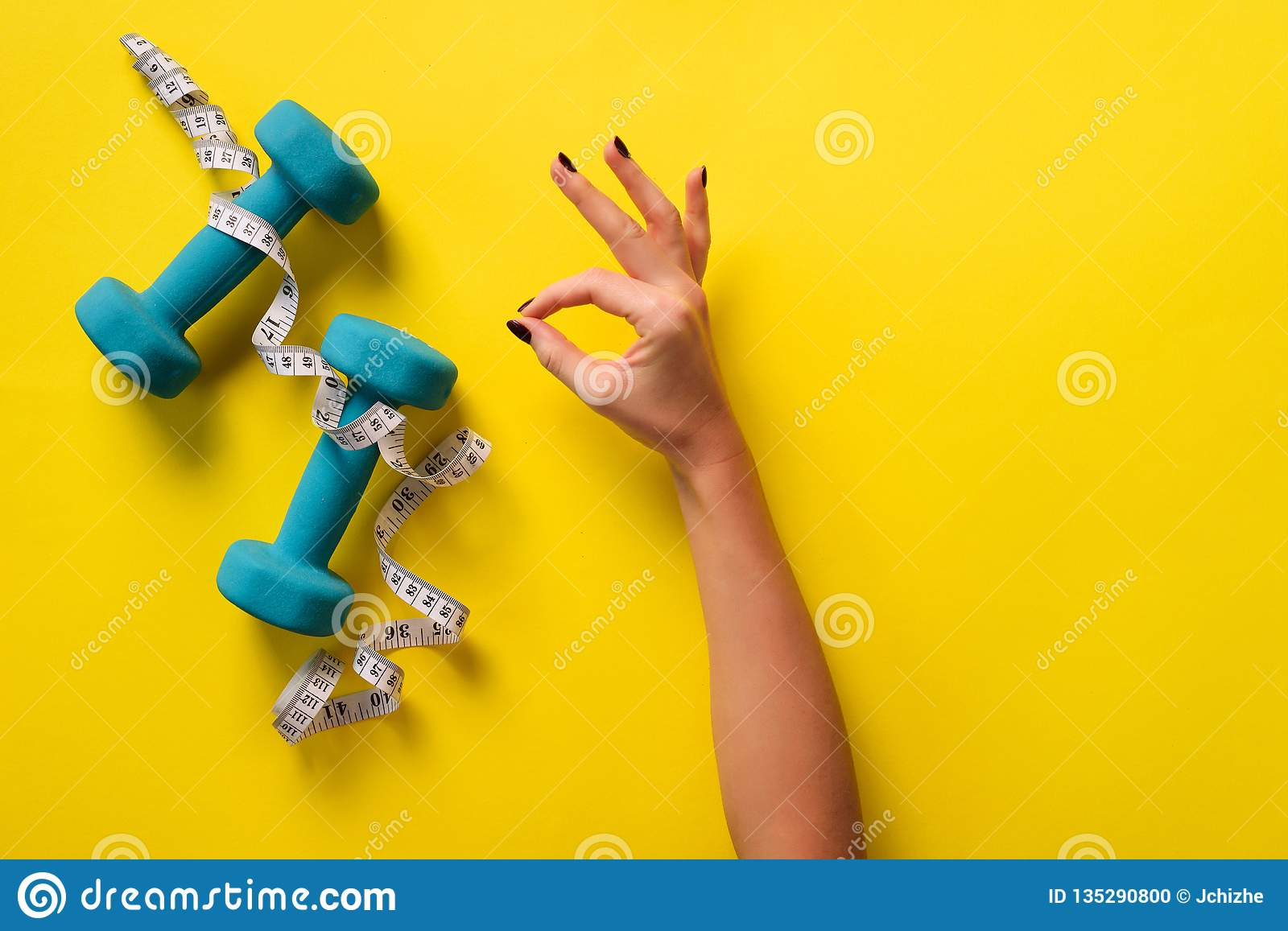 Female hand showing ok, like sign, measuring tape, dumbbells over yellow background. Top view, flat lay. Weight lost, sport,