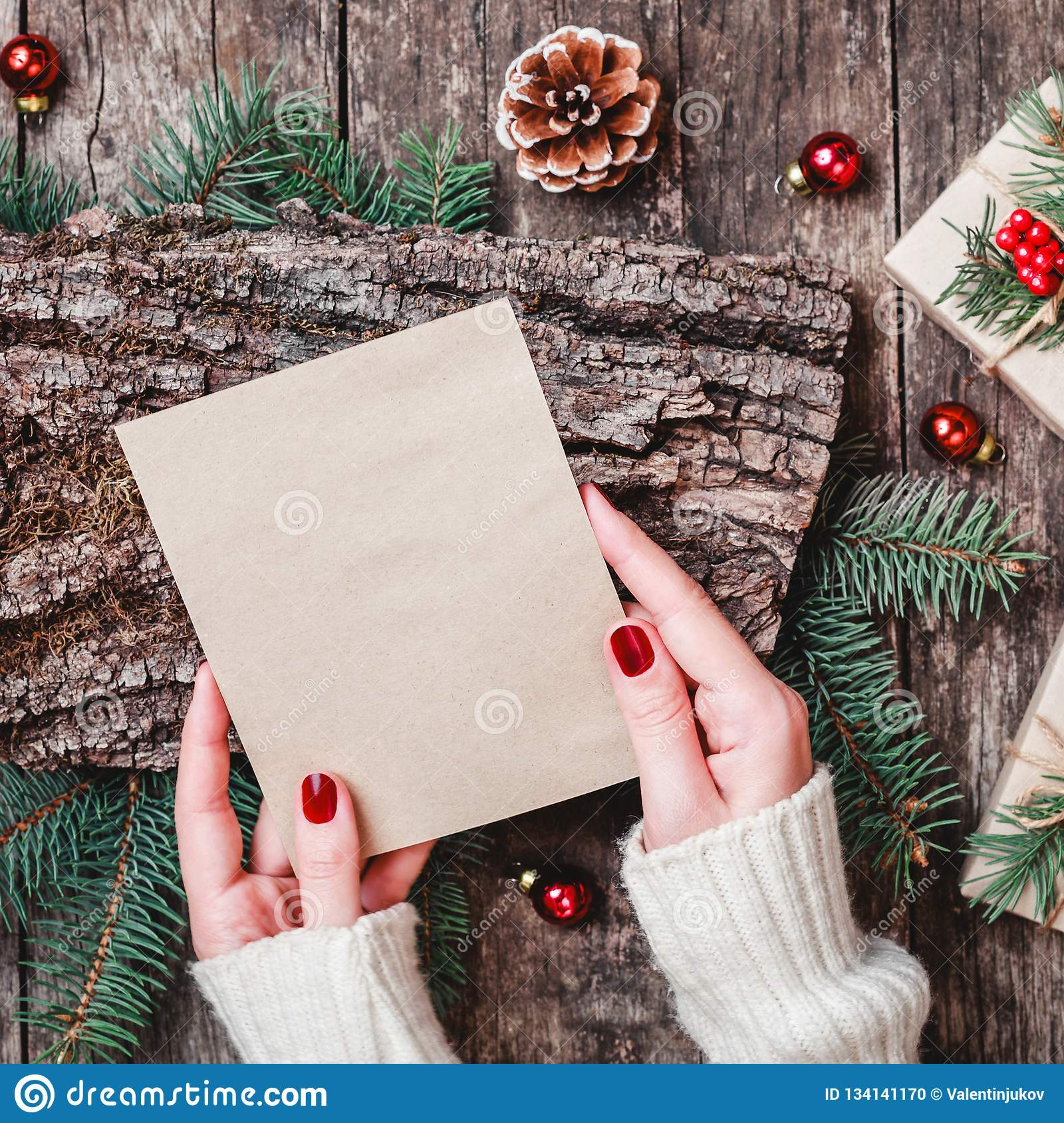 Female Hand Writing A Letter To Santa On Wooden Background With