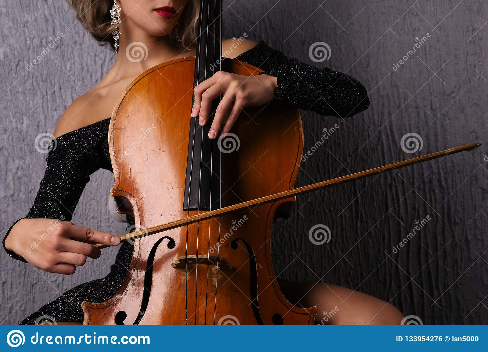 Female hands with a bow on cello strings