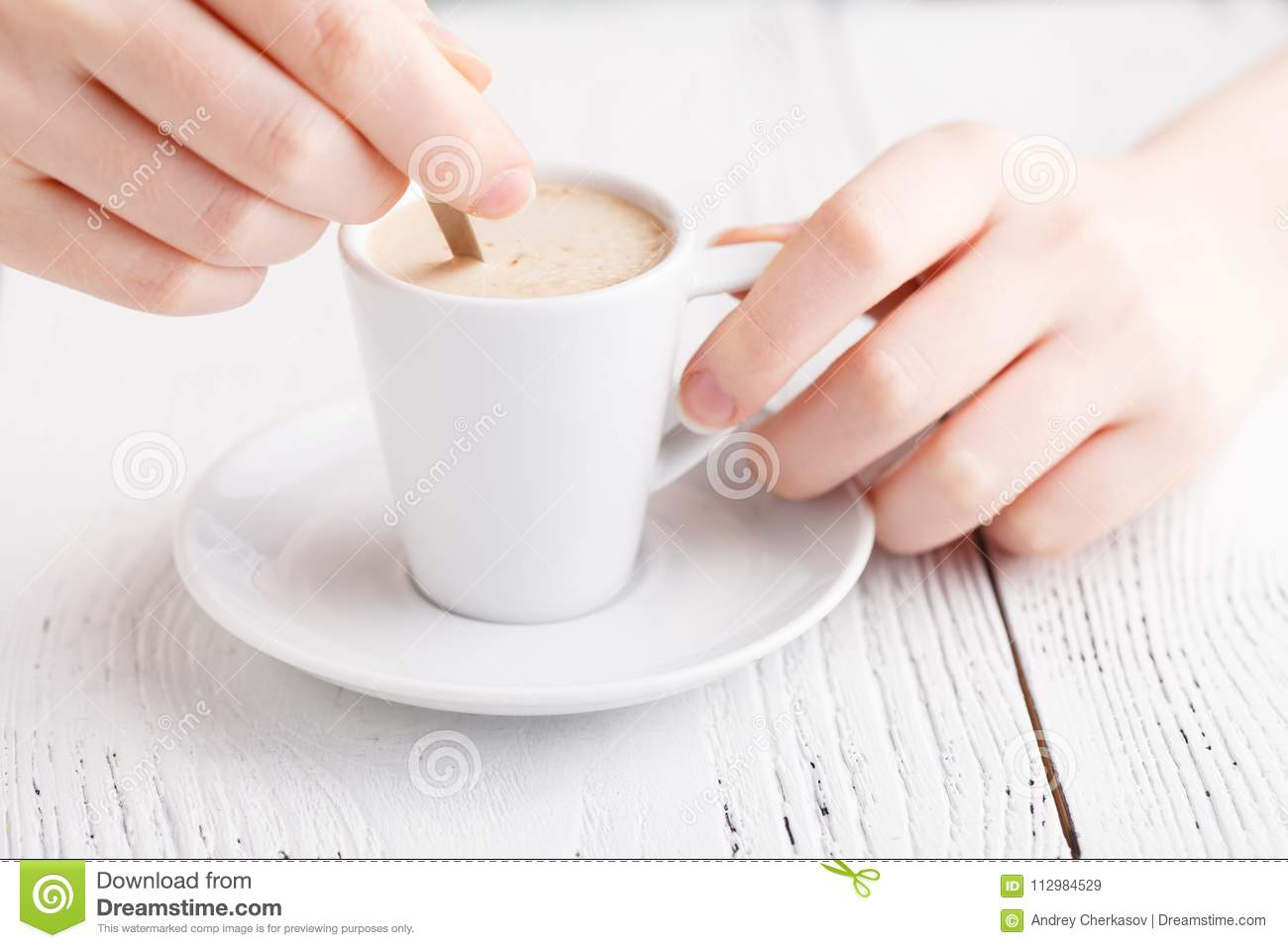 Female hands with a cappuccino cup in a cafe