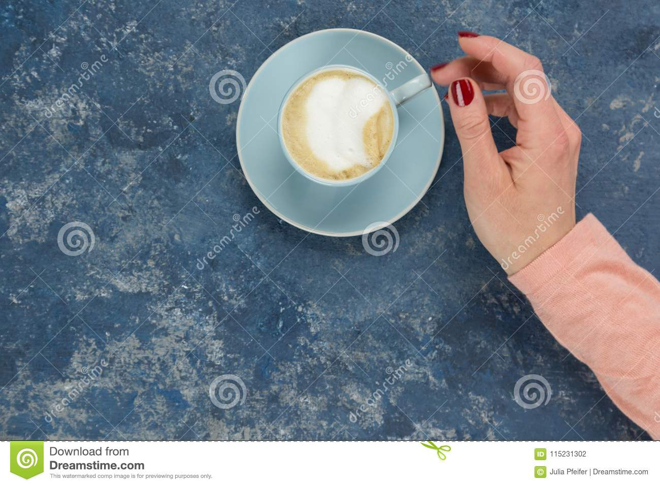 Female Hands With Cup Of Cappuccino Against Blue ...