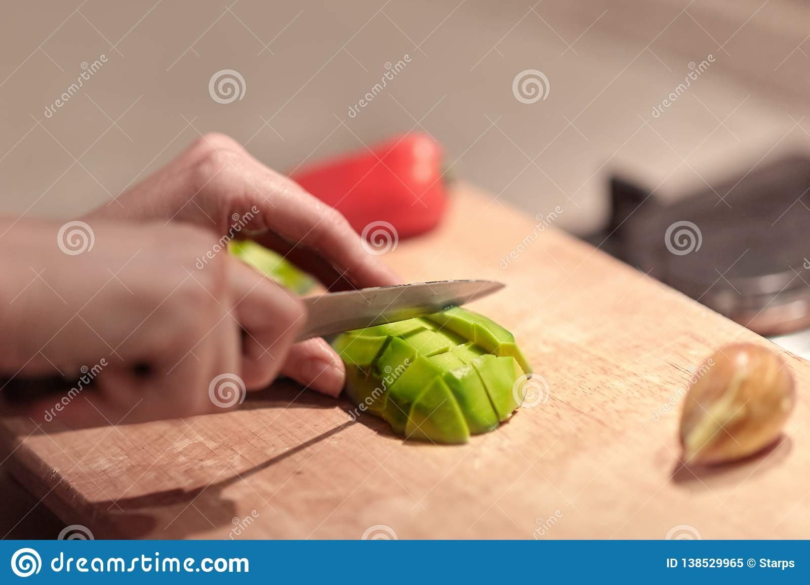 Female hands cutting fresh organic avocado with knife on wooden board in kitchen. Red bell pepper on background.