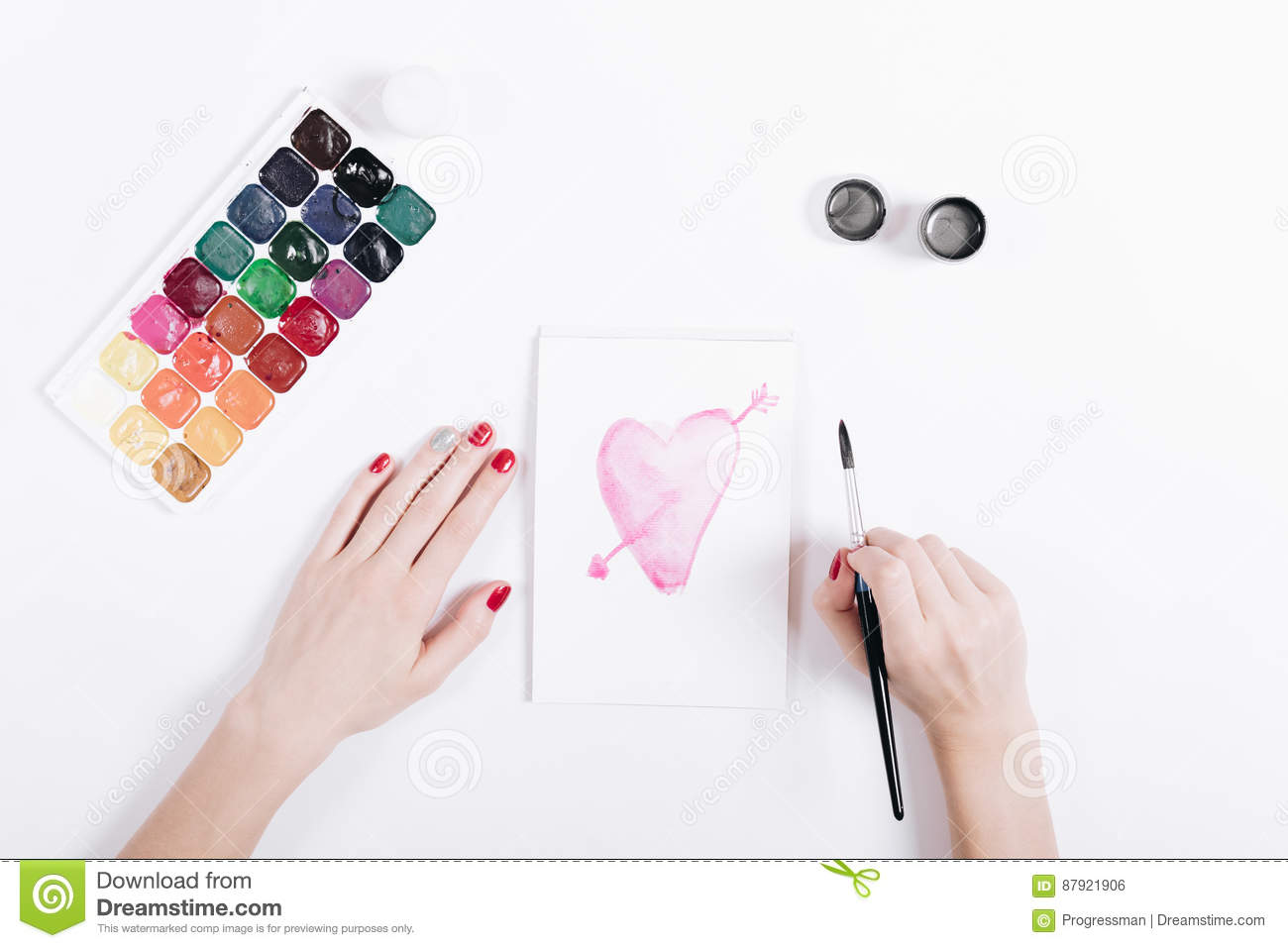 Female hands drawing with watercolors pink heart