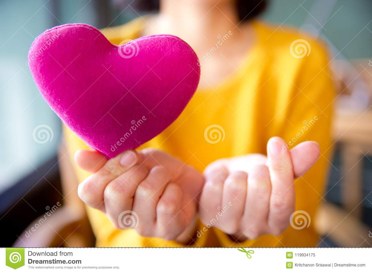 Female hands giving pink heart pillow and make a symbol of heart love with fingers.