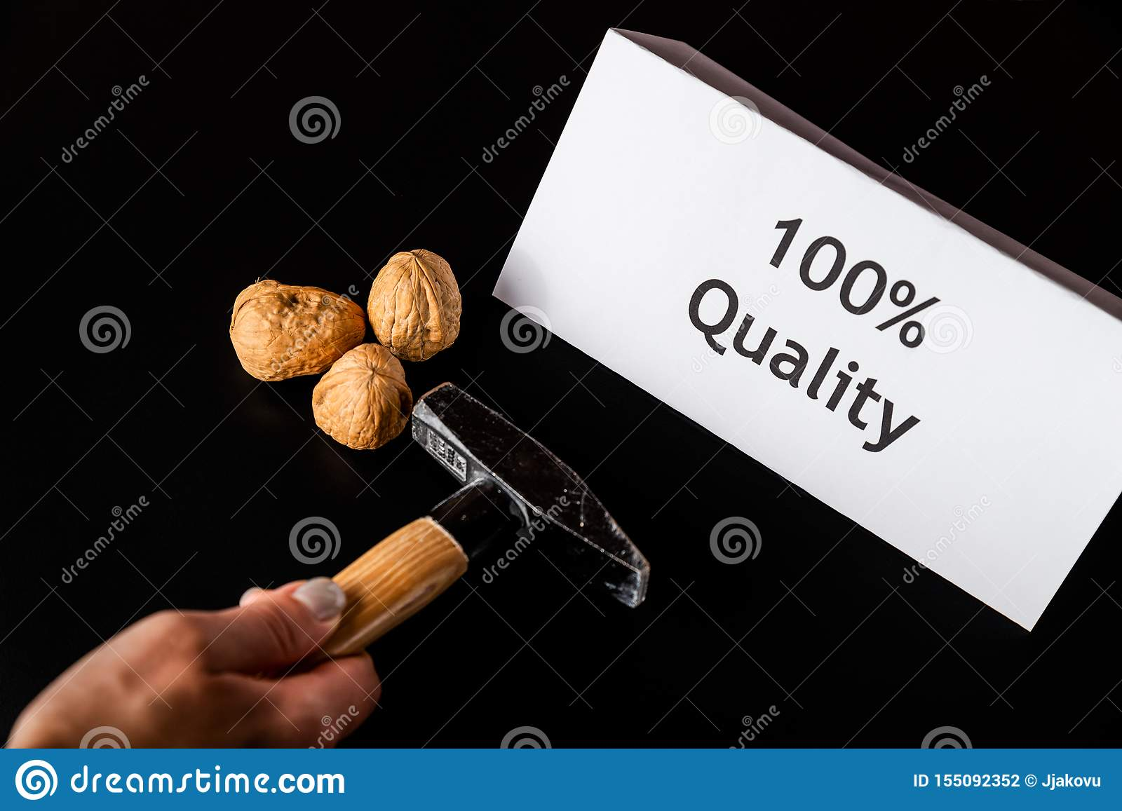 Female hands with hammer is beating three walnuts on the black table/background. The white paper/note `100  Quality` is near on th