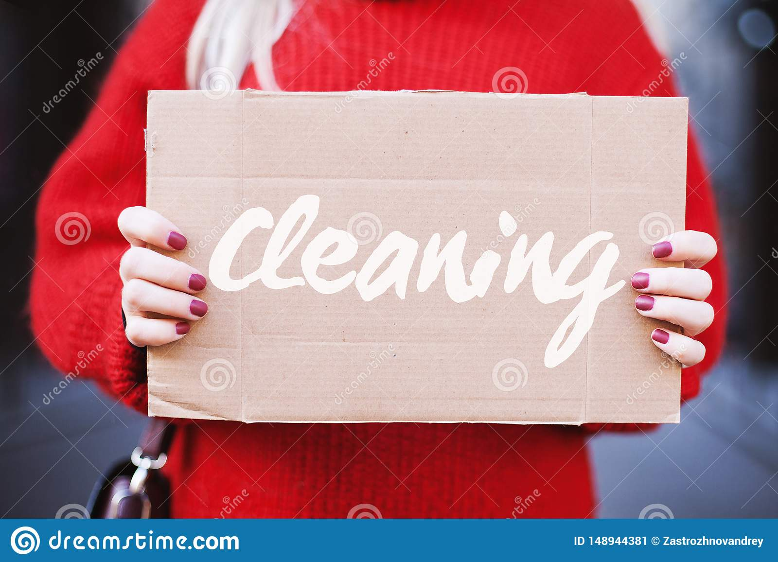 Female hands hold a cardboard tablet with the word `cleaning`, close-up.