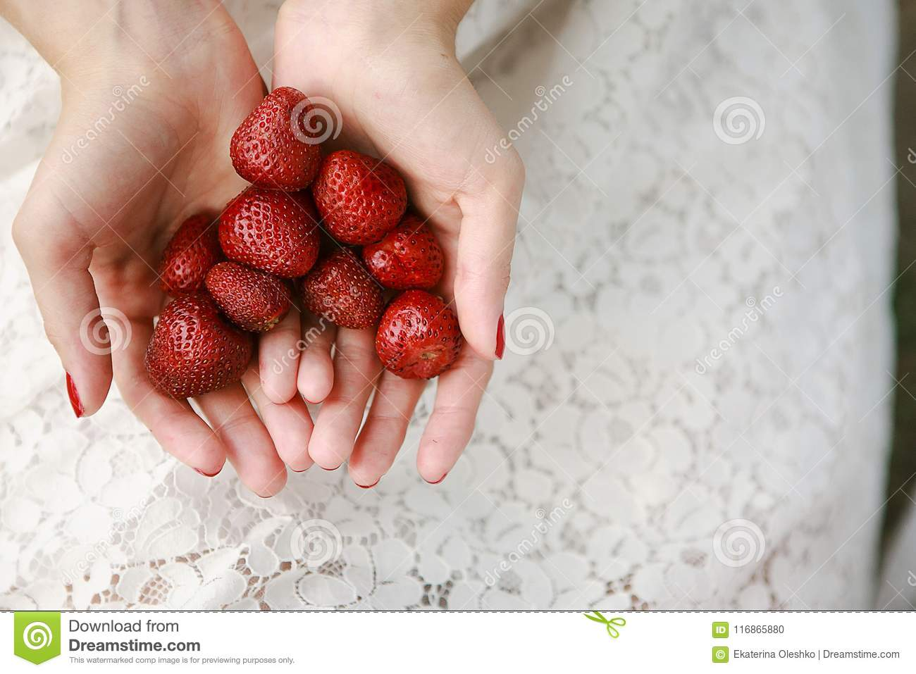 Female hands hold a handful of strawberries