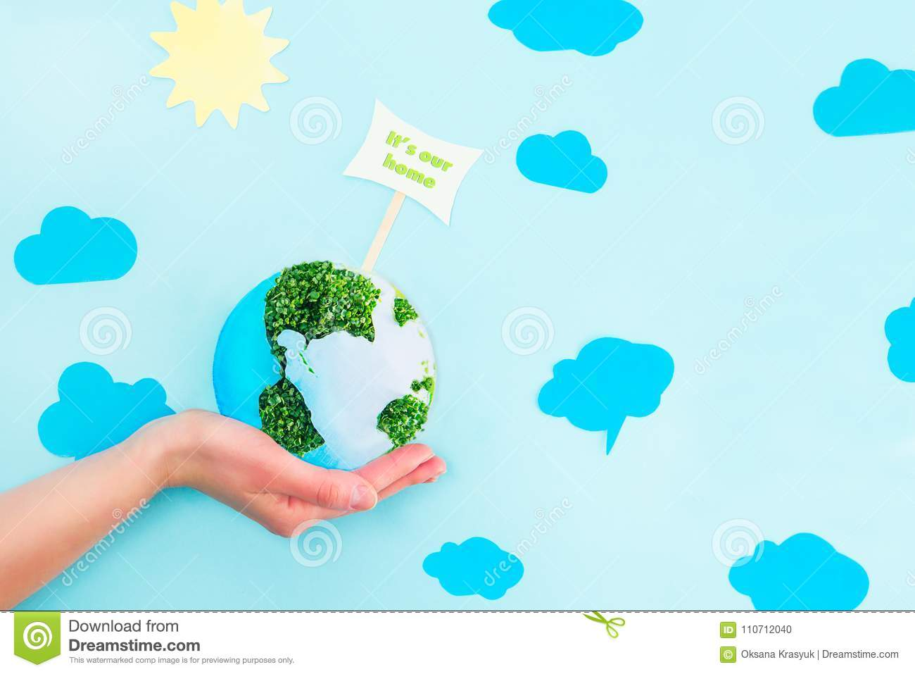 Female Hands holding Earth paper and green sprouts collage model with It`s our home pointer on blue background with paper sun and