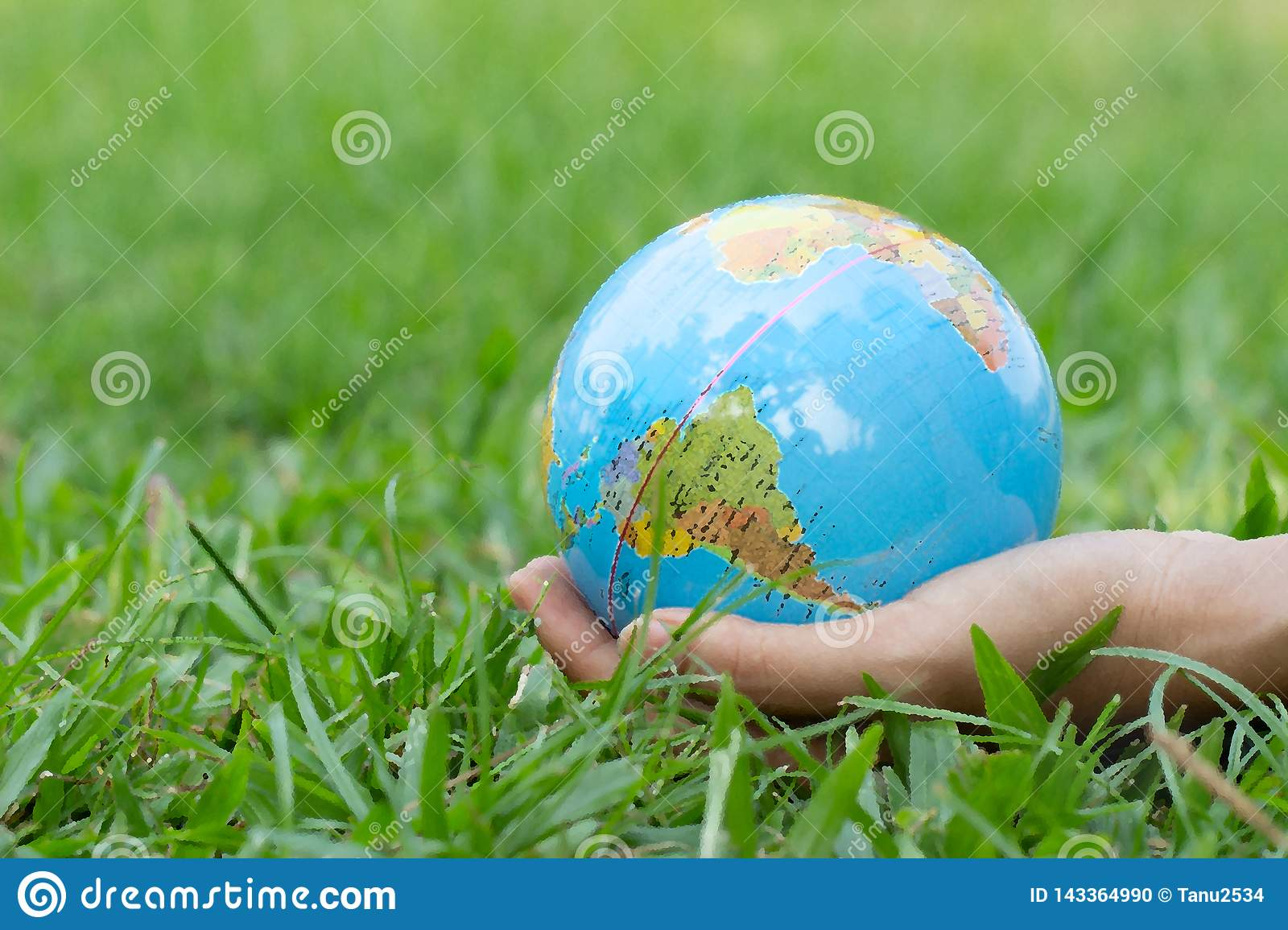 Female hands holding floating earth on natural green background. Earth day.