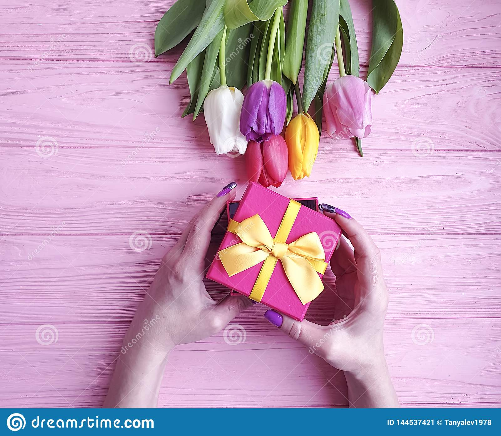 Female hands holding a gift box present birthday , romantic a bouquet of tulips on a wooden background