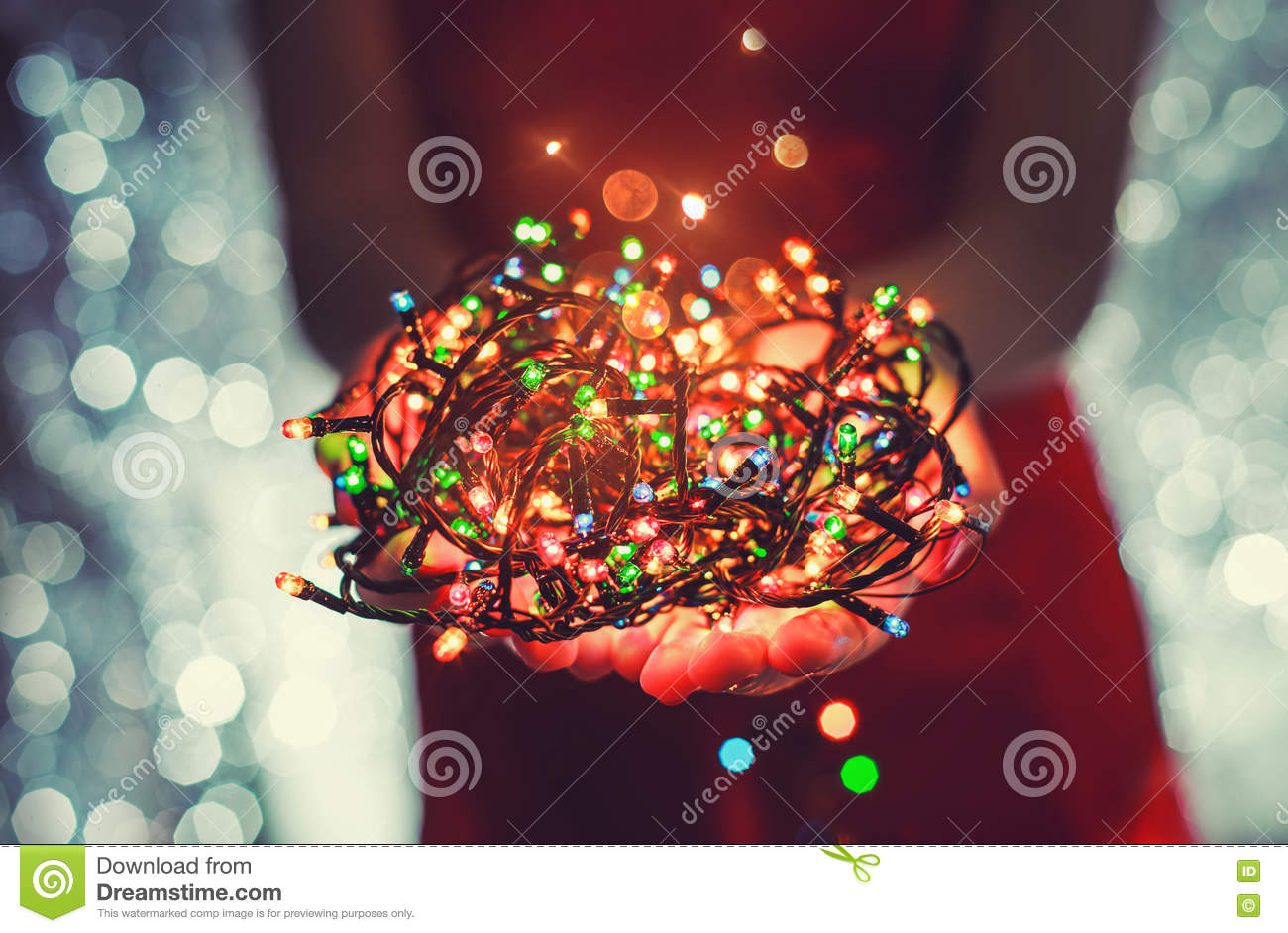 female hands holding multicolored christmas light decorations on dark holiday background xmas and new year