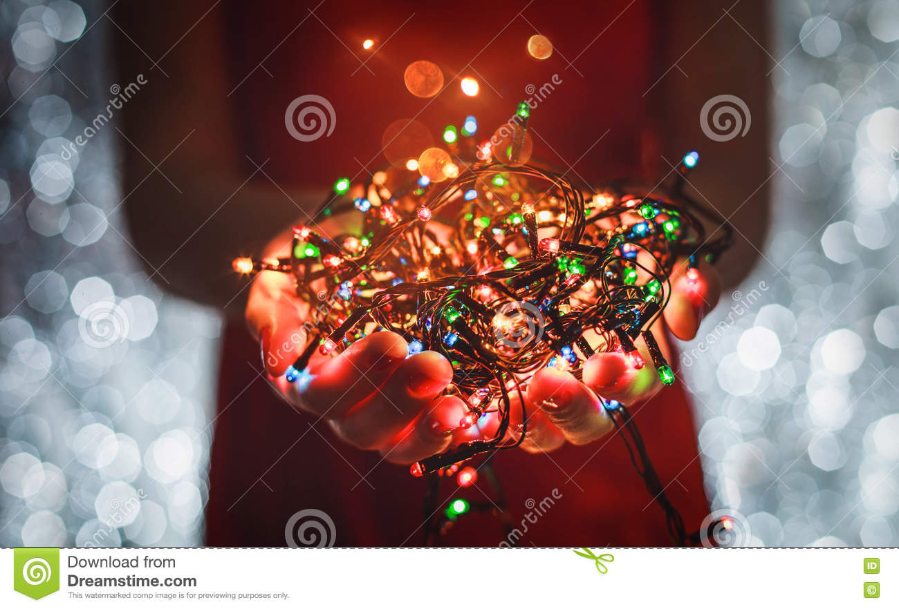 female hands holding multicolored christmas light decorations on dark holiday background xmas and new year theme toning