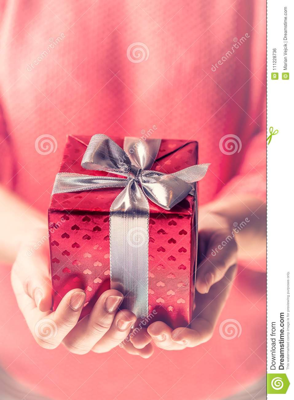 Female Hands Holding A Red Gift Wrapped With Silver Ribbon. Stock ...