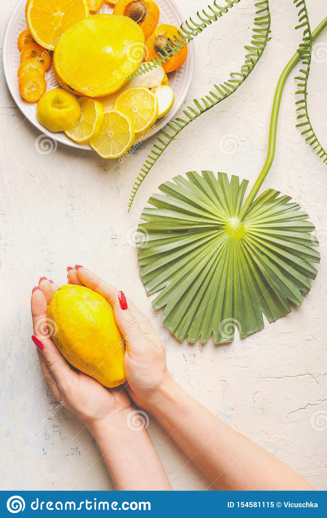 Female hands holding whole papaya fruit on white table with tropical leaves and plate with yellow sliced fruits, top view. Summer