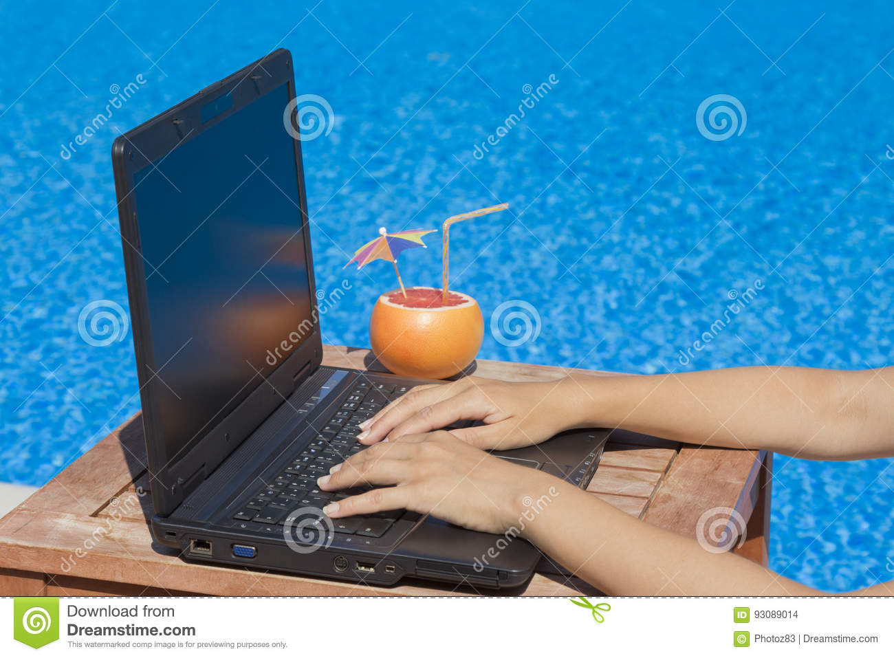 Female hands on laptop keyboard at the poolside