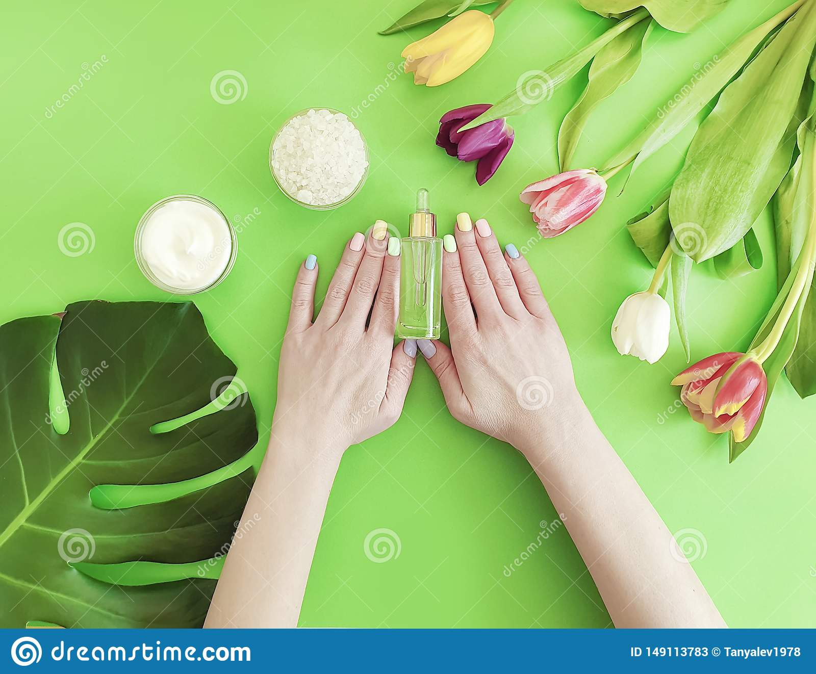 Female hands manicure, essence creative moisturizer summer therapy cream cosmetic tulip on a colored background