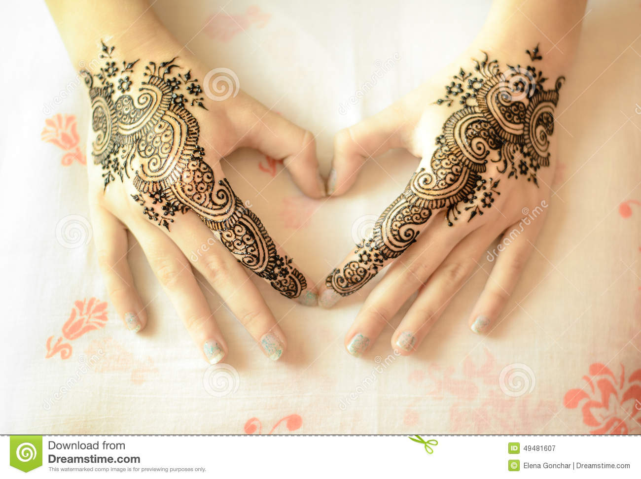 female hands with mehndi decoration in heart shape stock