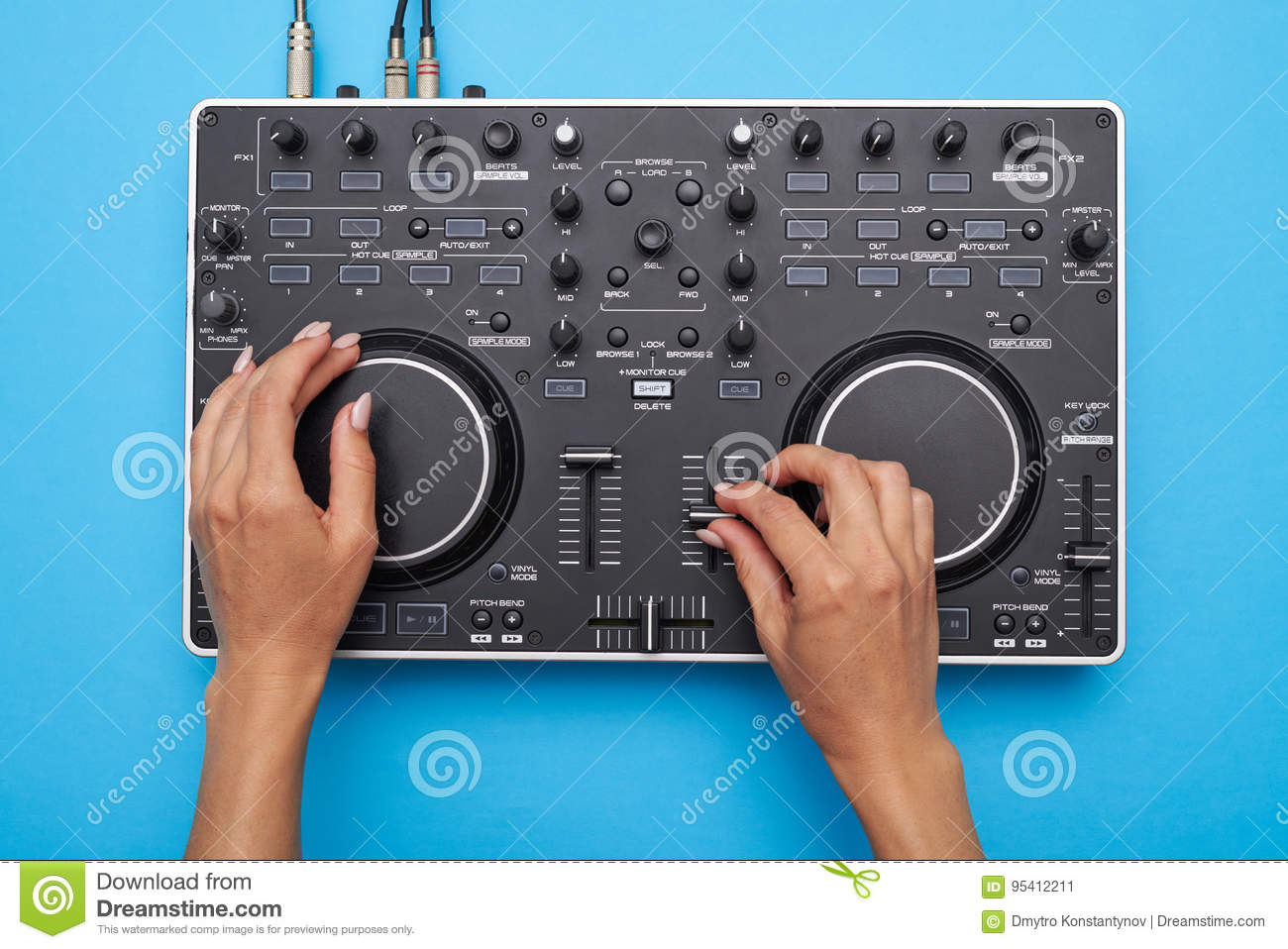 Female hands playing DJ mixer on blue background
