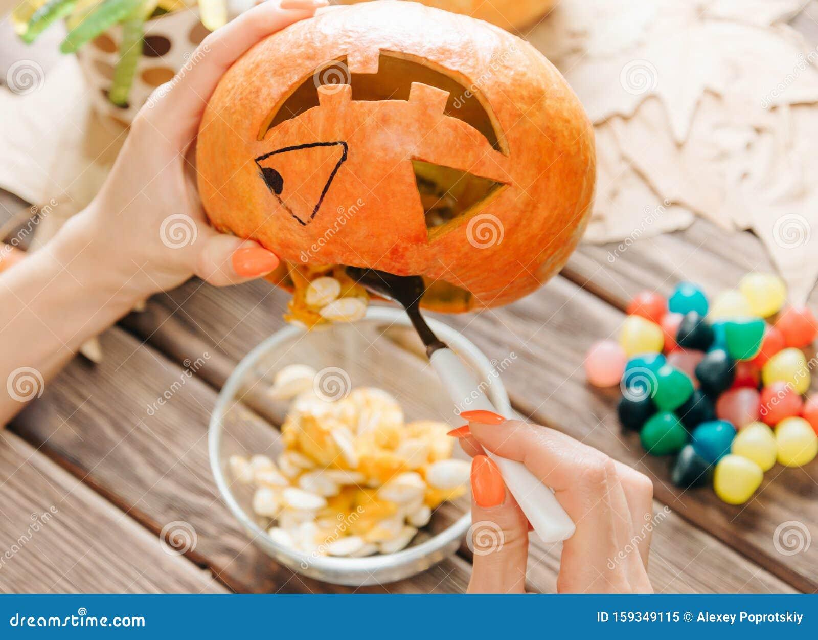 Female hands preparing jack-o-lantern pumpkin for Halloween.